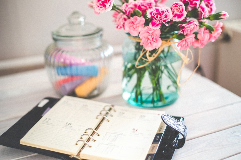 Open diary calendar on desk with flowers